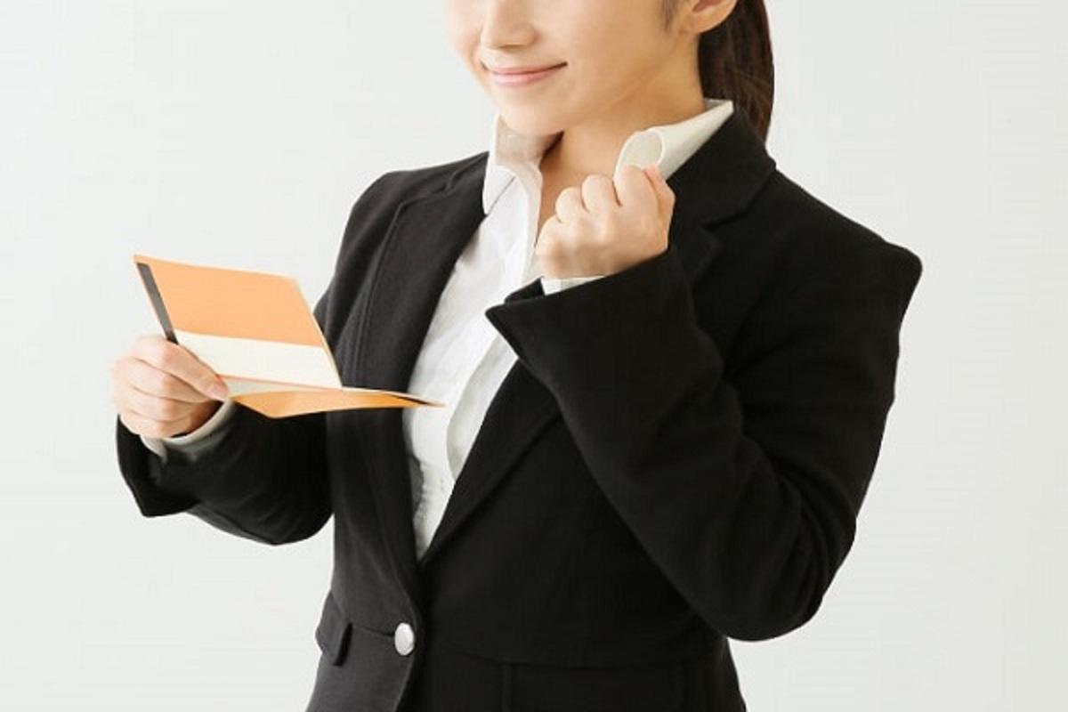 通帳を見てガッツポーズをする女性の画像