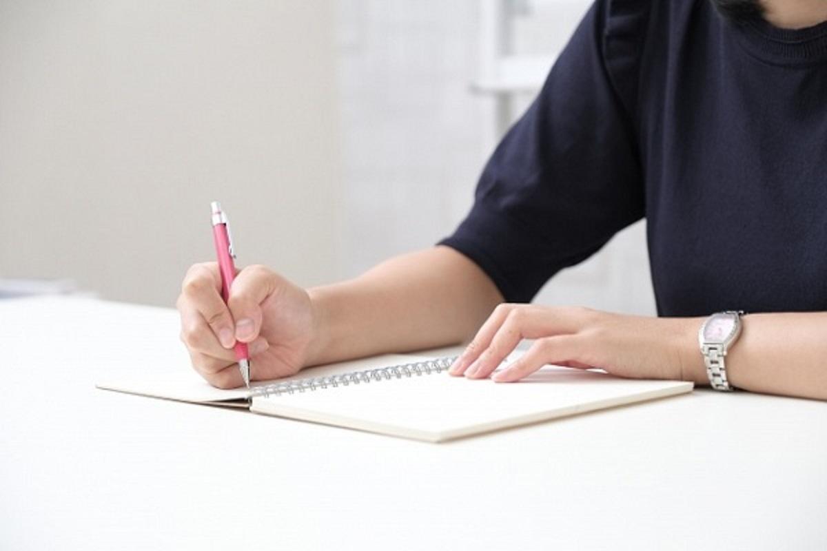 ノートにメモをしている女性の画像