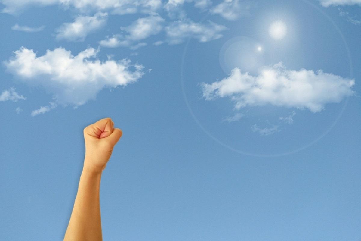 握りこぶしを空に掲げる画像